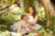 Woman in white tutu in forest setting breastfeeding her toddler for breasfeeding photoshoot