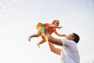 happy-father-holds-charming-little-girl-up-summer-sky.jpg