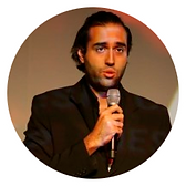 Foto Rodrigo. Está discursando com um microfone. Veste um blazer preto.