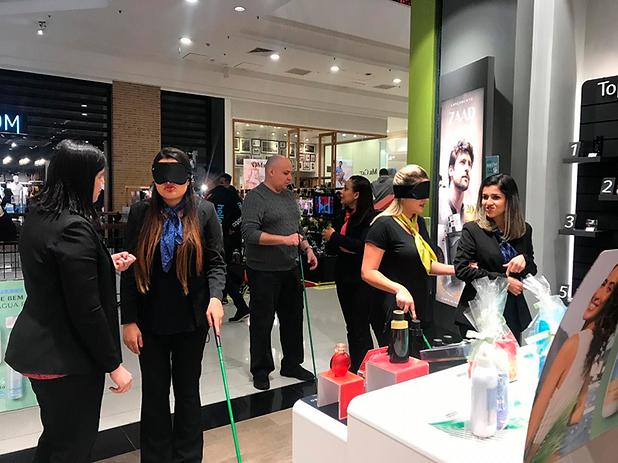 Foto de um treinamento feito pela Inclue. Mostra o sócio Sonny instruindo as vendedoras da Boticário enquanto estão de olhos vendados.