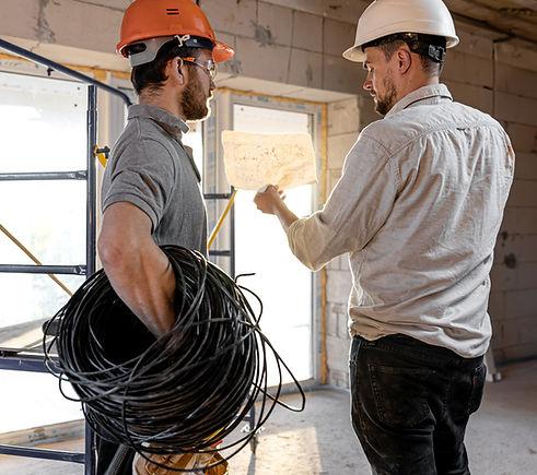 two-builder-engineers-talking-building-site-engineer-explaining-drawing-worker.jpg