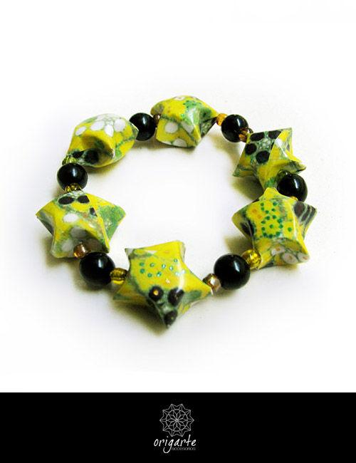 Pulsera simple de liga. Lleva estrellas amarillas, hechas con papel japones. Acompanadas por mostacillas y cuentas negras de acrlico