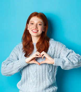 cute-redhead-girl-sweater-showing-heart-sign-i-love-you-gesture-smiling-camera-standing-ag