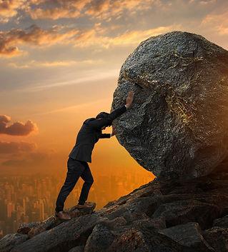 business-man-pushing-large-stone-up-hill