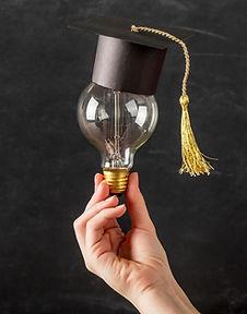 person-holding-light-bulb-with-graduation-cap.jpg