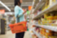 Woman is grocery shopping, she is holding a basket wit fruit while looking at items in a supermarket