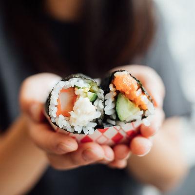 Tenant un rouleau de sushi