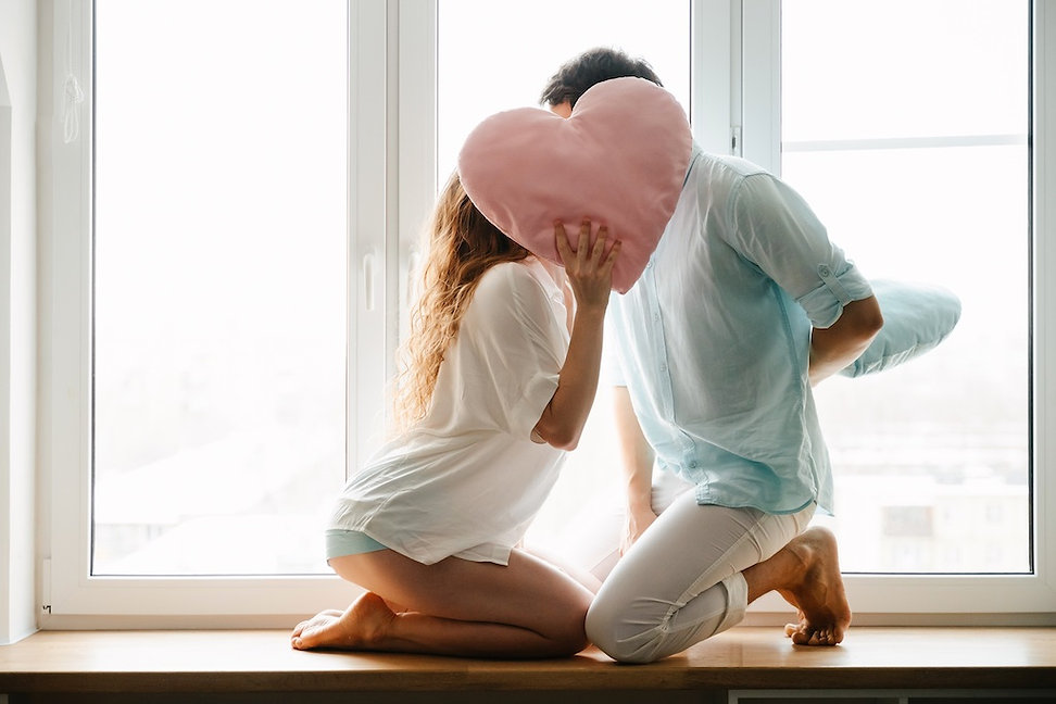 couple-girl-guy-play-with-pillows-near-w