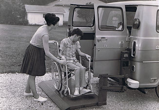 two women helping child in wheelchair into van