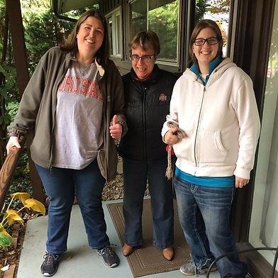 three adult females standing together outside home smiling friends roommates