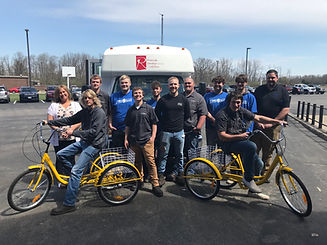group of male students smiling and posing with two yellow tricycles in front of a bus with adult female and adult males parking lot donors donations FANS friends allies and neighbors support service serve