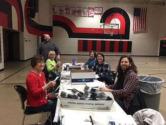 group of adults sitting around a table smiling and labeling newsletters volunteers FANS friends allies and neighbors volunteer service support mailing office work tasks