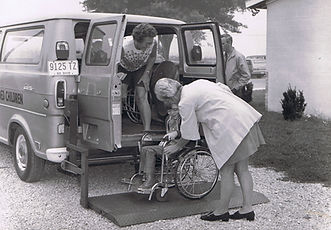 two adult females helping student in wheelchair into van child school education