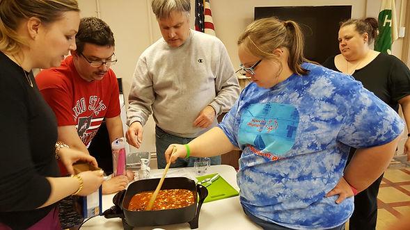 blonde adult woman stirring food in pan one adult woman, two adult men helping prepare food