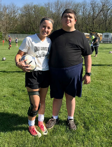 blonde female teenager standing with soccer ball and arm around young adult male with black hair