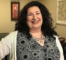 female with black hair smiling director leadership team professional headshot