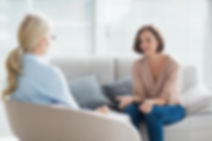 A woman is at a counseling session, she is sittig down on a sofa with her arms extended as if explaining