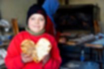Syrian boy holding up manaaesh in shape of heart, lebanon