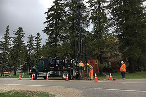 Truck-mounted drill-rig advancing boreholes in roadway