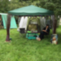 Photo of us beneath a green tent, attending the Barefoot Festival taht links to additional photos from the event