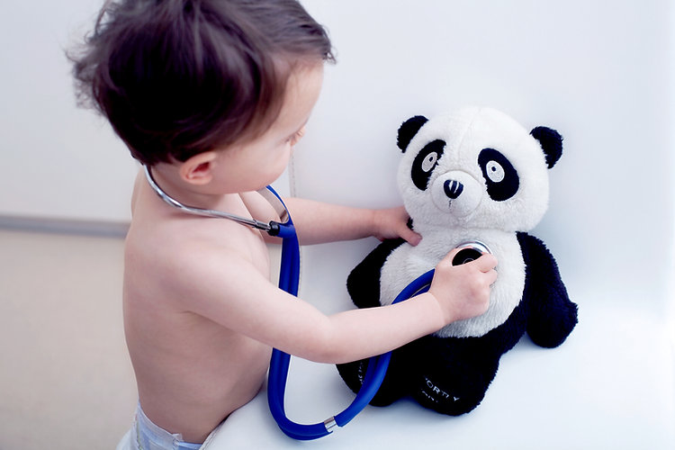 baby with stethoscope playing doctor with teddy bear