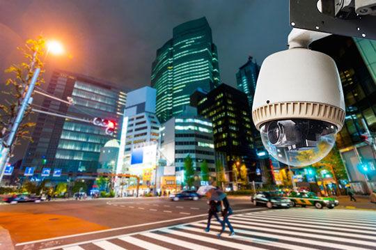 Camera de vigilâcia pendurada na rua a noite e com duas  caminhando