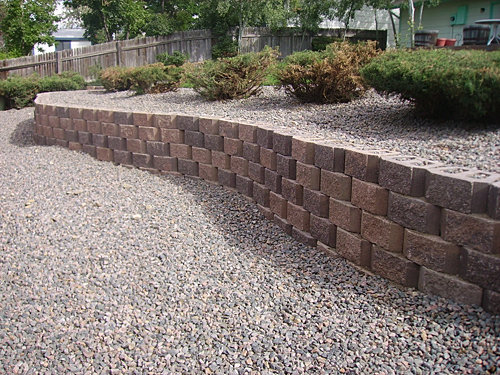 Retaining Wall Backyard Slope : Retaining wall with mountain granite rock separates sloping yard into