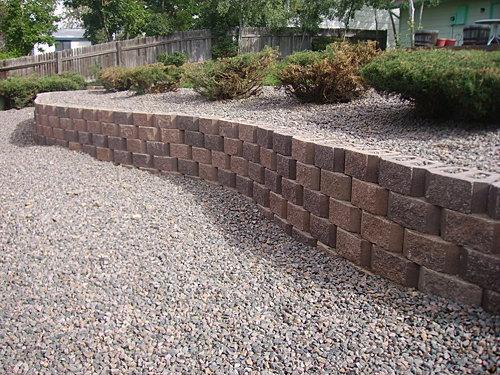 Retaining Wall Backyard Slope : Retaining wall with mountain granite rock separates sloping yard into