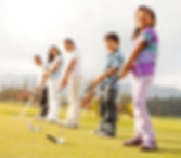 Golf players of all ages practicing to h