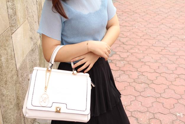 Fashionisa utilizando bolsa feminina branca de mão com look casual.