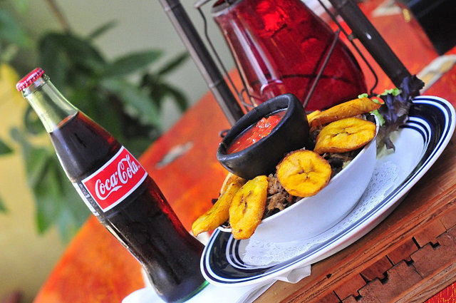 a brown wood table top with a glass bottle of coca cola, a bowl with salsa and plantains.