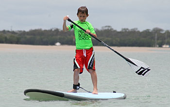 Child receiving Stand Up Paddle Board Lessons at Bargara