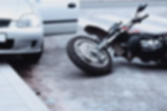 Motorcycle lying on the road and car sta