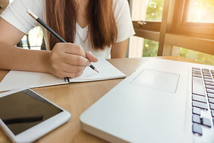 female-student-taking-notes-from-book-at-library-young-asian-woman-sitting-at-table-doing-