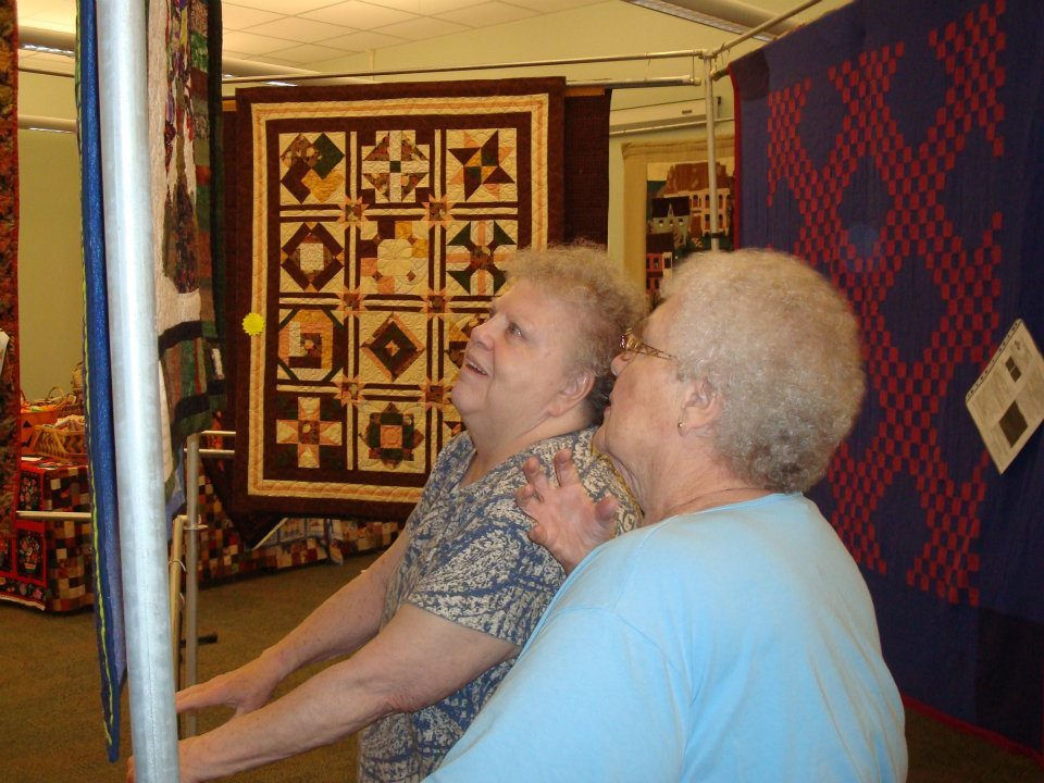 two ladies look at quilts.jpg