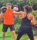 Personal trainer boxing with a female client outdoors