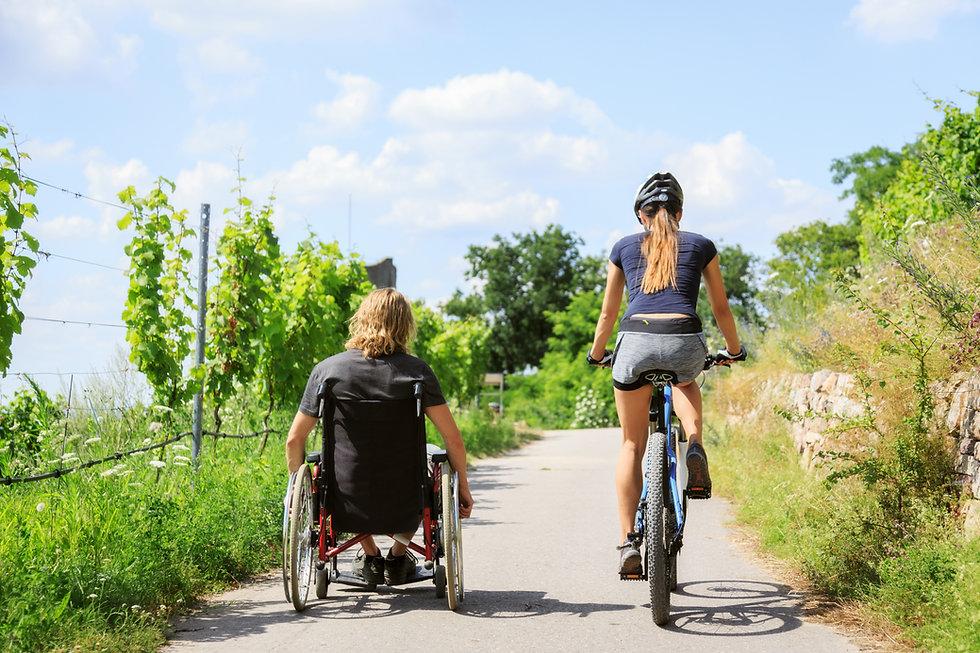 Par, desfrutando, ao ar livre. A mulher está de bicileta enquanto o homem está a acompanhando de cadeira de rodas.
