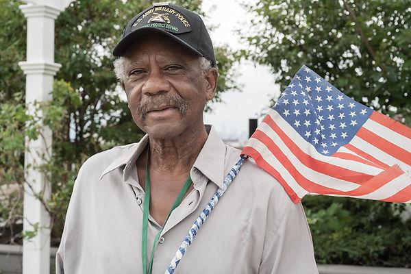 Senior man with an American flag.  Photo by Matt Oner