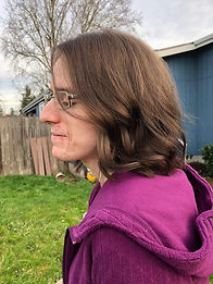 Woman in purple coat standing in her yard