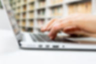 Closeup picture of a person typing on a laptop