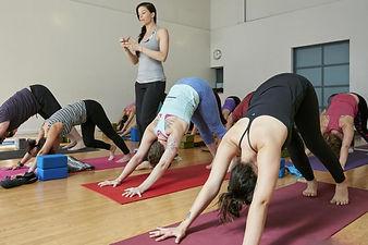 yoga-instructor-downward-facing-dog-clas