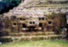 Closeup of jaguar face with earrings on a Maya temple at Lamanai, Belize
