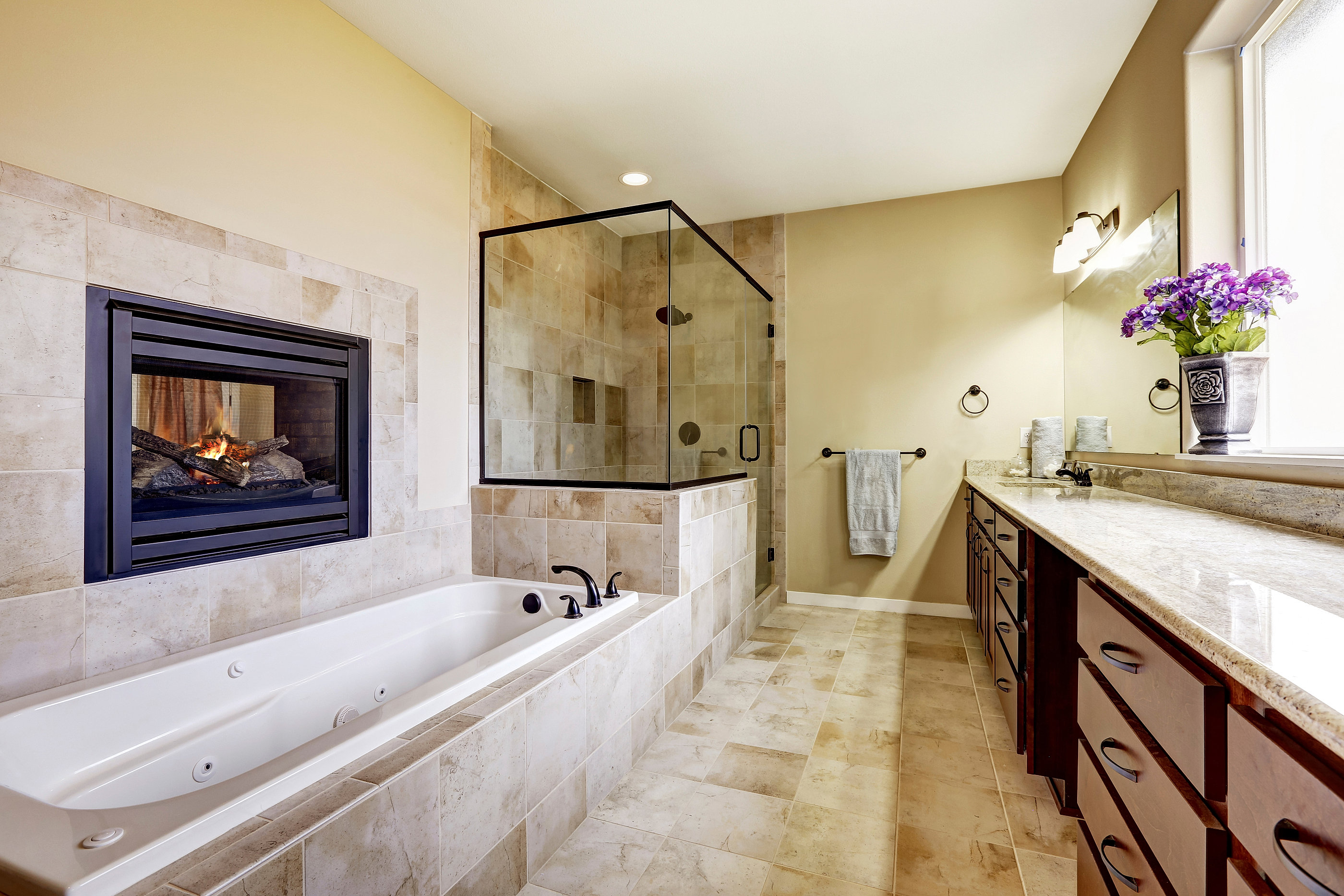 modern mansion master bathroom in house with fireplace and tile
