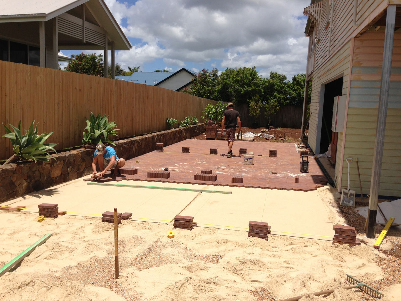 A rock wall is used as the retaining wall and a paved driveway is added.