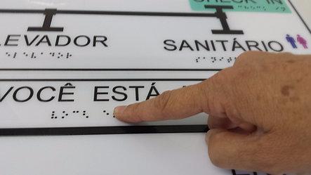 Exemplo de mapa tátil. Vê-se parte da palavra Elevador. À direita está a palavra Sanitário. Abaixo das palavras em tinta há a inscrição em braile. Um dedo está sobre um dos pontos pretos.