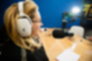 Blonde woman speaking into microphone while recording podcast in a recording studio.