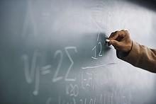 Teacher Writing a Formula on a Blackboard