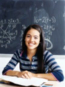 Student sitting in front of a chalk board
