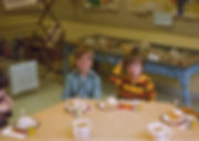 two boys sitting at a snack table