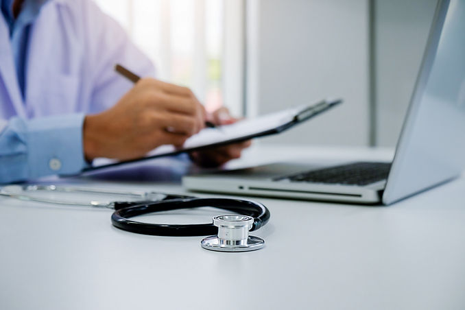 Doctor working at laptop with clipboard and stethoscope